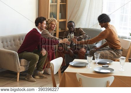 Multi-ethnic Group Of Contemporary Adult People Clinking Champagne Glasses While Enjoying Dinner Par