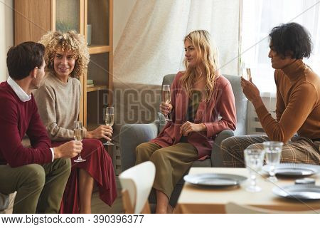 Multi-ethnic Group Of Contemporary Young People Drinking Champagne And Chatting While Sitting On Cou