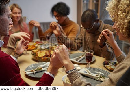 Multi-ethnic Group Of People Holding Hands While Praying At Thanksgiving Dinner With Friends And Fam