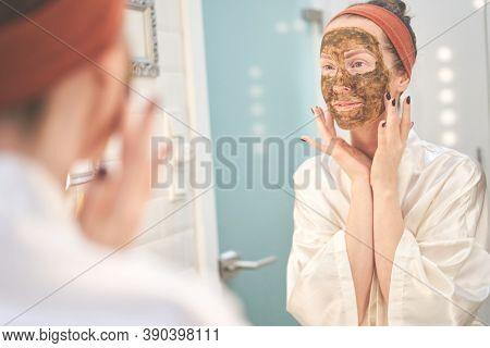 Woman cosmetic facial skin care. Woman in skin rubber peeling face beauty mask.