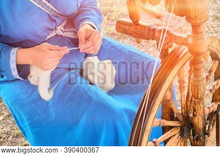 Spinning Wheel Is A Device For Manual Spinning Of One Yarn Thread. The Spinner - Woman, Engaged In H