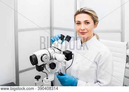 Portrait Positive Gynecologist Woman Sitting Near A Colposcope In Her Gynecological Office. Gynecolo
