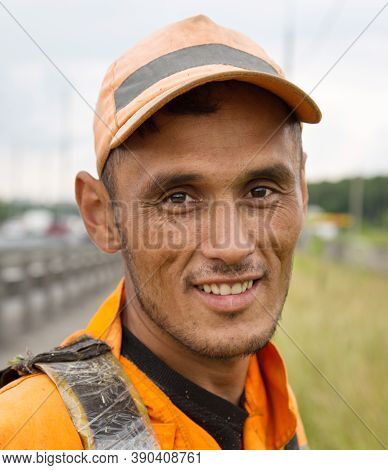 Portrait Of Happy Worker In A Bright Orange Dress Against The Backdrop Of The Construction Of Roads,