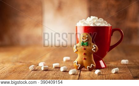 Christmas homemade gingerbread cookie and cup of hot chocolate with marshmallow on wooden table. Christmas food and drink concept