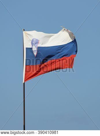Slovenian Flag Flying On Flagpole On Blue Sky Background