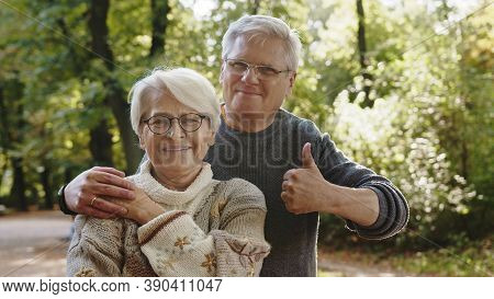 Happy Old Couple Hugging In Park. Senior Man Flirting With Elderly Woman. Thumbs Up. High Quality Ph