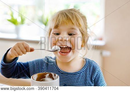 Adorable Toddler Girl Drinking Hot Milk With Froth. Happy Healthy Child Indoors, Enjoying Chocolate