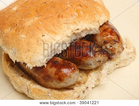 Char-grilled sausages in a wholemeal bread bap