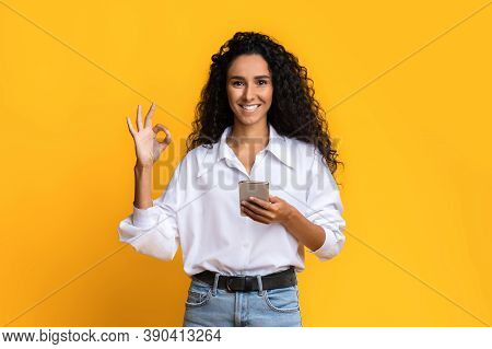 Great Mobile Offer. Smiling Young Woman Holding Smartphone And Showing Ok Gesture, Recommending New