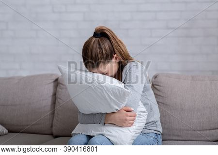 Young Woman With Depression Hugging Pillow And Crying On Sofa At Home. Lonely Millennial Lady Feelin