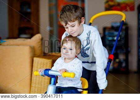Little Kid Boy Pushing Bycicle Or Tricycle With Cute Baby Sister. Toddler Girl And Brother Playing T