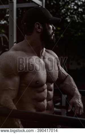 Strong Young Male Athlete With Beard And Perfect Muscle Physique Body Wearing Black Cap Resting Duri