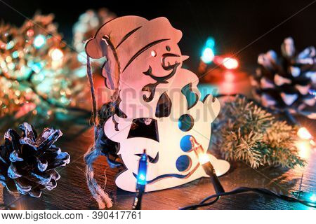 Christmas Or New Year Background With Wooden Decorative Snowman, Pine Cone, Christmas Lights And Fir
