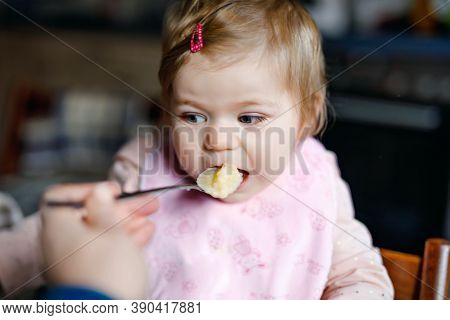Adorable Baby Girl Eating From Spoon Mashed Vegetables And Puree. Food, Child, Feeding And People Co