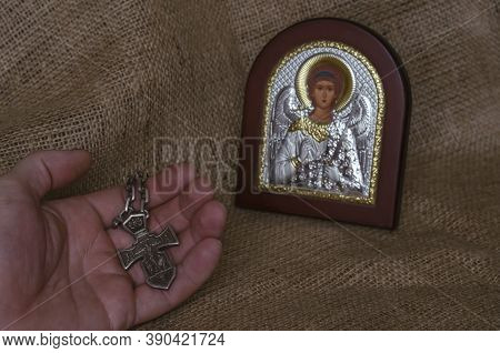 Christian Orthodox Icon Of The Archangel Michael And A Hand With A Silver Cross. Male Hand With A Pe