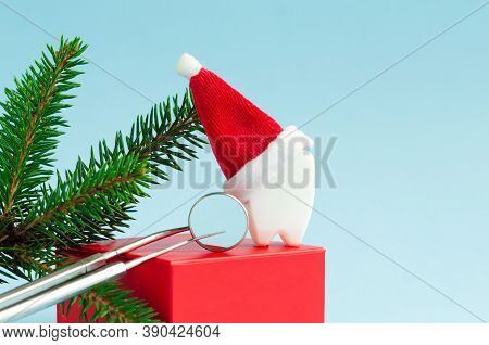 Toy Tooth In Santa Hat With Mirror And Probe, Spruce Branch On Red Podium, On Blue Background For Th