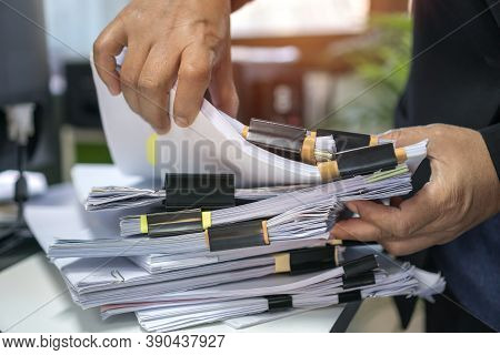 Office Workers Arranging Stacks Of Lot Paperwork Files For Searching Infomation Unfinished Documents