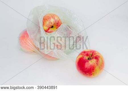 Transparent Plastic Crumpled Cellophane Bag With Group Of Ripe Red Yellow Apples On A White Backgrou