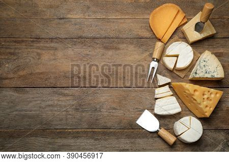 Set Of Different Cheeses And Specialized Knives And Fork On Wooden Table, Flat Lay. Space For Text