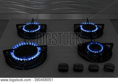 Modern Gas Cooktop With Burning Blue Flames In Kitchen At Night