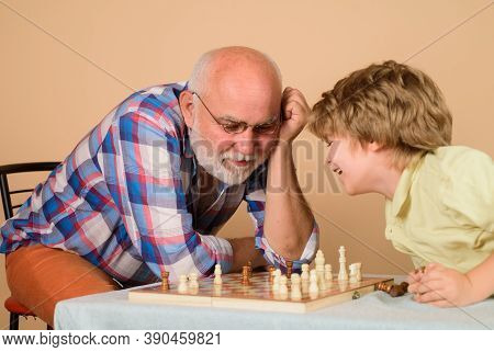 Chess. Kid Playing Chess With Grandpa. Grandfather Teaching Grandson Play Chess. Family Relationship