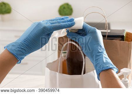 Woman Cleaning Newly Purchased Bottle Of Juice With Antiseptic Wipe Indoors, Closeup. Preventive Mea