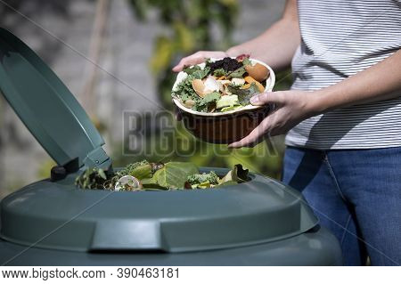 Close Up Of Woman Emptying Food Waste Into Garden Composter At Home
