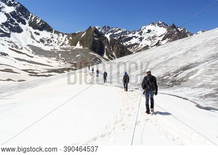 Rope Team Mountaineering With Crampons On Glacier Taschachferner And Mountain Snow Panorama With Blu