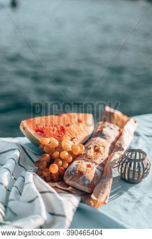 Summer Picnic On A Beach. Fresh Watermelon, French Baguette And Grapes On A Blanket. Vertical Photo