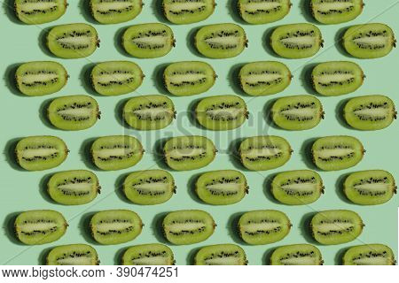 Kiwi Pattern. Repetition Of Kiwi Halves On A Light Green Background. Colorful Food Background. Fruit
