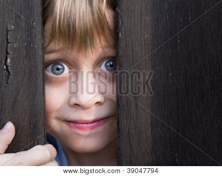 young boy looking through wooden barrier