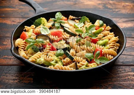 Fusilli Pasta With Vegetable, Broccoli, Zucchini, Red Pepper, Eggplant And Basil In Iron Cast Pan