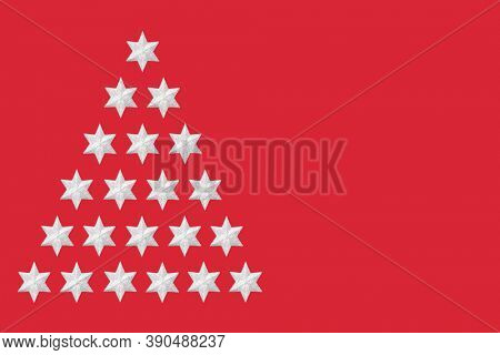 Abstract silver star Christmas tree concept on red background. Festive minimal design for the xmas holiday season.