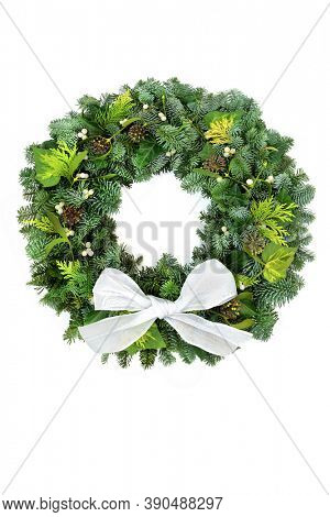Natural Christmas winter greenery wreath for Christmas with spruce fir, cedar cypress leaves, ivy & mistletoe on white background with bow. Traditional symbol for the xmas festive season & New Year.