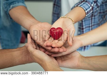 Close up of friends hands holding a red heart shape. Top view of young men and women hands showing small red heart. Multiethnic guys and girls holding a heart-shaped stone symbol of love and care.