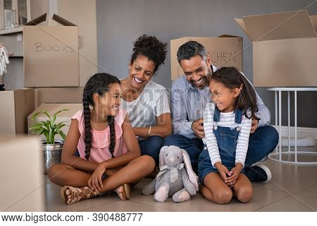Cheerful young multiethnic parents talking and playing with daughters while sitting on floor in new house. Indian man family tickles and jokes with his little girl after relocating to new home.