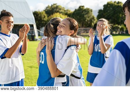 Happy football players hugging on field after scoring a goal. Soccer teammates embracing while players clapping hands on victory. Successful girl soccer players celebrating after winning the match.