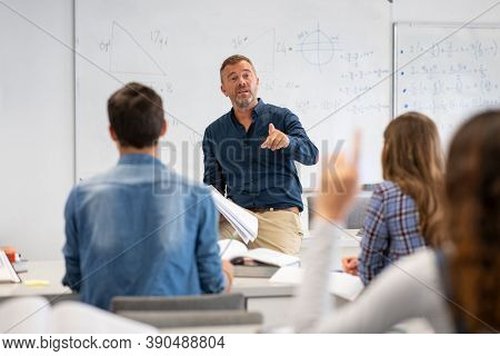 Professor pointing at college student with hand raised in classroom. Student raising a hand with a question for the teacher. Lecturer teaching in class while girl have a question to do during a lesson
