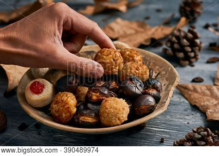 closeup of a man taking a panellet, a typical confection of Catalonia, Spain, eaten traditionally in All Saints Day, from a plate with some more and a roasted sweet potato and some roasted chestnuts