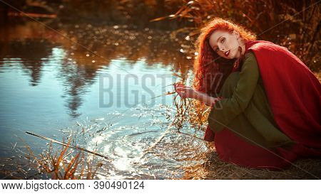 Beautiful red haired girl in a traditional green celtic dress and a red cloak sits by the lake. Historical reconstruction of ancient Celtic times.