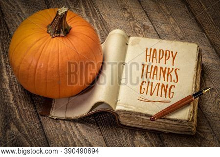 Happy Thanksgiving - handwriting in a retro, leatherbound journal with a pumpkin against rustic wood, fall holiday greetings