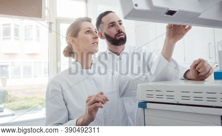 Two doctors looking at a screen with patient data discussing what they see