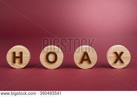 Hoax Sign On A Wooden Circles On Red