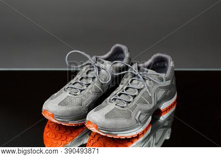 trekking sneakers with red sole, gray background
