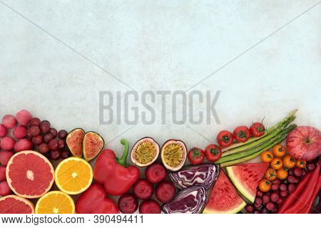 Fruit & vegetable border on mottled background. Foods very high in lycopene and also high in antioxidants, anthocyanins, minerals, vitamins & dietary fibre. Healthy heart & immune boosting food.