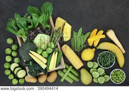 Yellow & green high fibre fruit & vegetables also high in antioxidants, protein, vitamins, minerals & smart carbs. Healthy eating concept. Top view, flat lay, copy space on slate background.