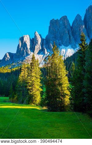 Sunset, Majestic Dolomites. Italy. Powerful mountain peaks surround the piicturesque green valley Val di Funes. The concept of active, ecological and photo tourism