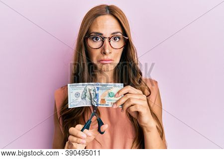 Young brunette woman cutting dollars with scissors for currency devaluation depressed and worry for distress, crying angry and afraid. sad expression.