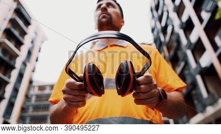 Builder Covers His Ears, Ear Muff To Protect Workers Ears. Construction Worker Wearing Protective Ea