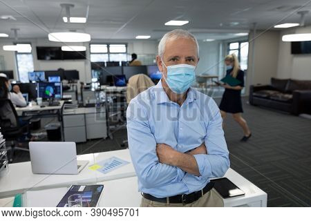 Portrait of senior Caucasian businessman wearing face mask working in a modern office, standing with arms crossed looking to camera. Hygiene in workplace during Coronavirus Covid 19 pandemic.